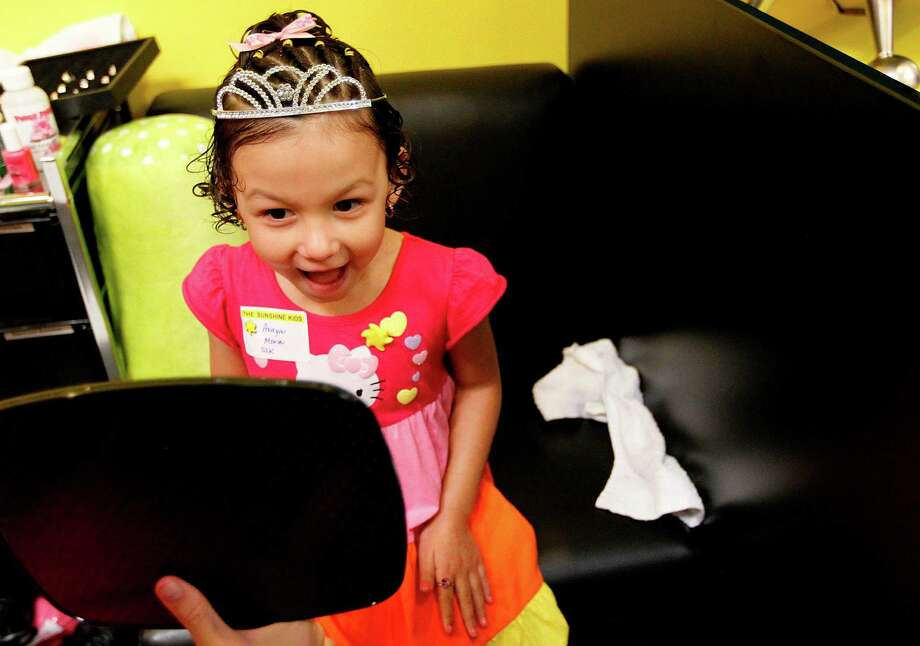 "Avaya Mora, 5, smiles when she sees herself wearing a princess' tiara during a ""Princesses for a Day"" event. Six Sunshine Kids are princesses for a day as they get hair styling, manicures, and wear princess dresses during a karaoke style Princess Party. The girls also got to meet Disney Princess characters, then to see Disney On Ice: Dare to Dream.  ( Mayra Beltran / Houston Chronicle ) Photo: Mayra Beltran, Houston Chronicle / © 2012 Houston Chronicle"
