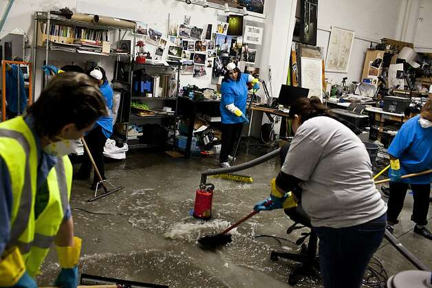 Employees with ServiceMaster Clean work to remove water from a shared studio at Workspace Limited Studios after early Thursday morning rain flooded many businesses and homes on Folsom Street in between 17th and 18th streets in San Francisco, Calif., April 12, 2012. Photo: Jason Henry, Special To The Chronicle