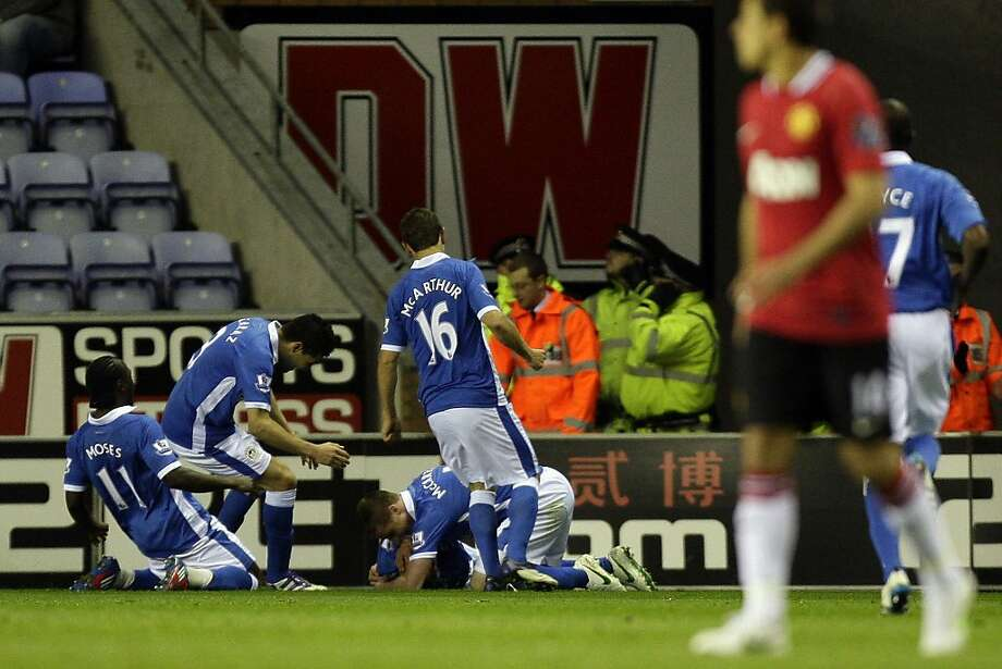 Wigan's Shaun Maloney, bottom centre, is mobbed by jubilant teammates after scoring against Manchester United during their English Premier League soccer match at The DW Stadium, Wigan, England, Wednesday, April 11, 2012. (AP Photo/Jon Super) Photo: Jon Super, Associated Press