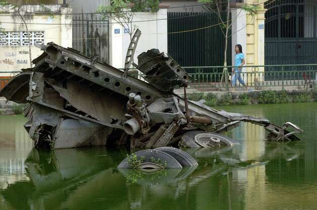 A woman walks near the wreckage of a B-52 in a small lake in Hanoi, Vietnam on Nov. 15, 2006. The bomber was  shot down in  1972. Photo: SHAH MARAI, AFP/Getty Images / 2006 AFP