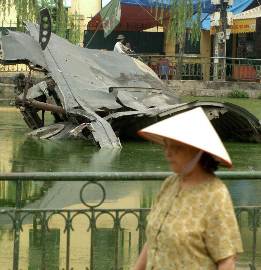 Hanoi, VIET NAM:  A woman walks near the wreckage of a U.S. B-52 shot down in 1972 on a small lake in Hanoi on Nov. 15, 2006. Photo: SHAH MARAI, AFP/Getty Images / 2006 AFP