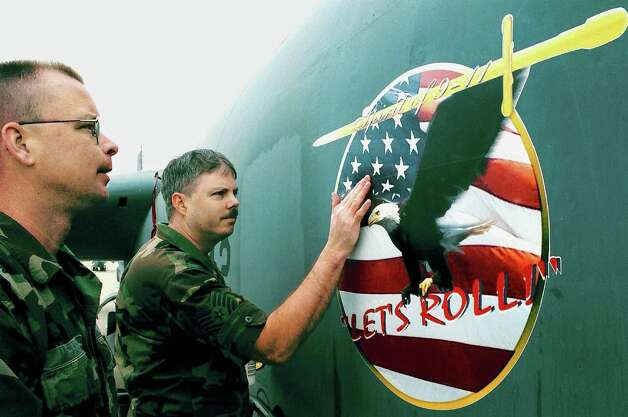"""U.S. Air Force Reservists Tech. Sgt. Ron (left) and Staff Sgt. Brian of the 93rd Bomber  Squadron apply a decal with the phrase """"Lets Roll"""" to the side of a B-52 bomber on Feb. 20, 2002 at Barksdale Air Force Base, La.  Photo: Mario Villafuerte, Getty Images / Getty Images North America"""