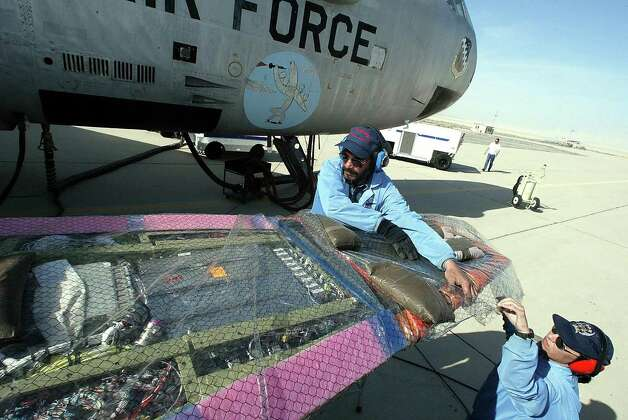 Engineering technicians Casey  Tull (right) and Charlie Nichols wrap up the  X-43 research vehicle, which is mated to a B-52 during test-flight prep on March 24 2004 at Edwards Air Force Base in California. Photo: ROBYN BECK, AFP/Getty Images / 2004 AFP