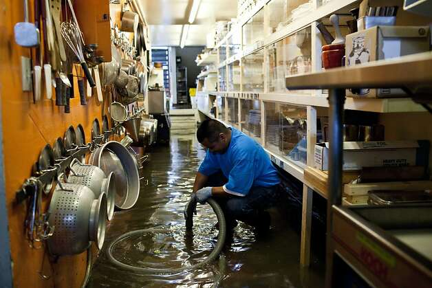 An employee with ServiceMaster Clean pumps water from the kitchen of Stable Cafe after early Thursday morning rain flooded many businesses and homes on Folsom Street in between 17th and 18th streets in San Francisco, Calif., April 12, 2012. Photo: Jason Henry, Special To The Chronicle
