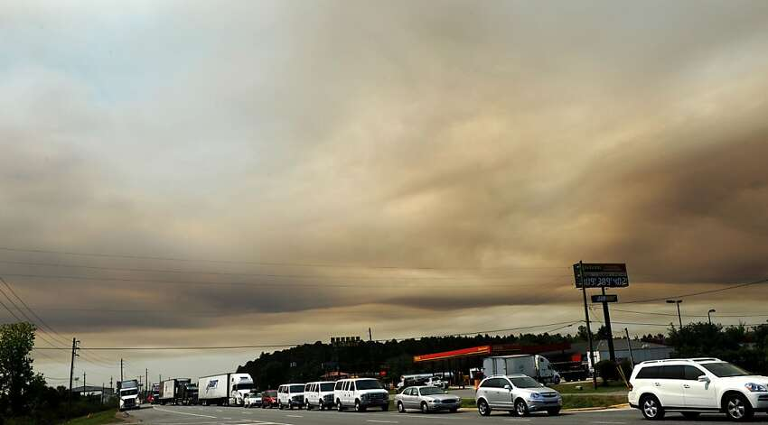 Cars line up on US-301 to go East on Interstate 10 as a smoky sky looms, Wednesday, April 11, 2012 in Jacksonville, Fla. (The Florida Times-Union, Bob Mack) TV OUT; MAGS OUT