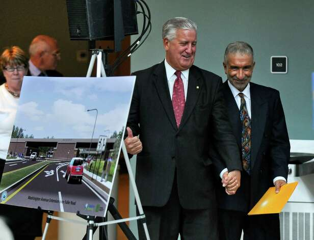 Albany Mayor Jerry Jennings, center, and College of Nanoscale Science and Engineering Senior Vice President and CEO Dr. Alain Kaloyeros, right, laugh as they hold hands and walk to the podium at the start of an event to announce that the state DOT will begin highway improvements at the intersection of Fuller Road and Washingon Avenue Extension, at the Albany NanoCollege on Thursday April 12, 2012 in Albany, NY. State DOT Commissioner Joan McDonald, is behind them at far left, along with Congressman Paul Tonko, second from left.  (Philip Kamrass / Times Union ) Photo: Philip Kamrass / 00017221A