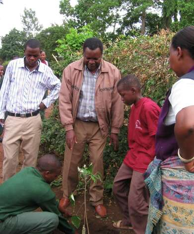 Sebastian Chuwa, a leading conservationist, helps the students plant trees. (Courtesy of Clarinets for Conservation)