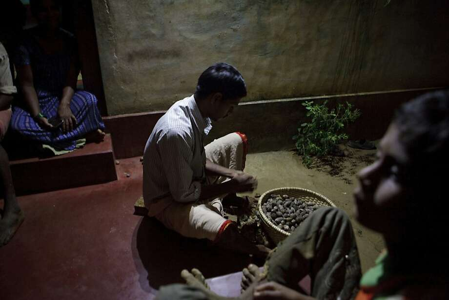 Anand, 25, peels betel nuts under lights powered by a Simpa Networks Inc. solar unit at his house in Halliberu village, Karnataka, India, on Wednesday, Jan. 11, 2012. Across India and Africa, startups and mobile phone companies are developing so-called microgrids, in which stand-alone generators power clusters of homes and businesses in places where electric utilities have never operated. Photographer: Kuni Takahashi/Bloomberg *** Local Caption *** Anand Photo: Kuni Takahashi, Bloomberg
