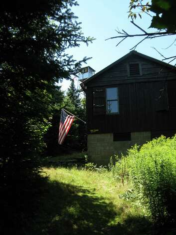 Photo by Herb Terns The observer's cabin at Balsam Lake Mountain with the firetower visible just over the roof. Volunteers have the option of spending the night in the cabin, but need to haul in all their food and water.