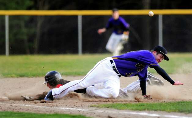 Voorheesville's third baseman Mike Young (34), left, tags out Chatham's Mike Dorato (4) when the ball takes a bad bounce during their baseball game on Thursday, April 12, 2012, at  Roger Keenholts Park in Guilderland, N.Y. (Cindy Schultz / Times Union) Photo: Cindy Schultz / 00017218A
