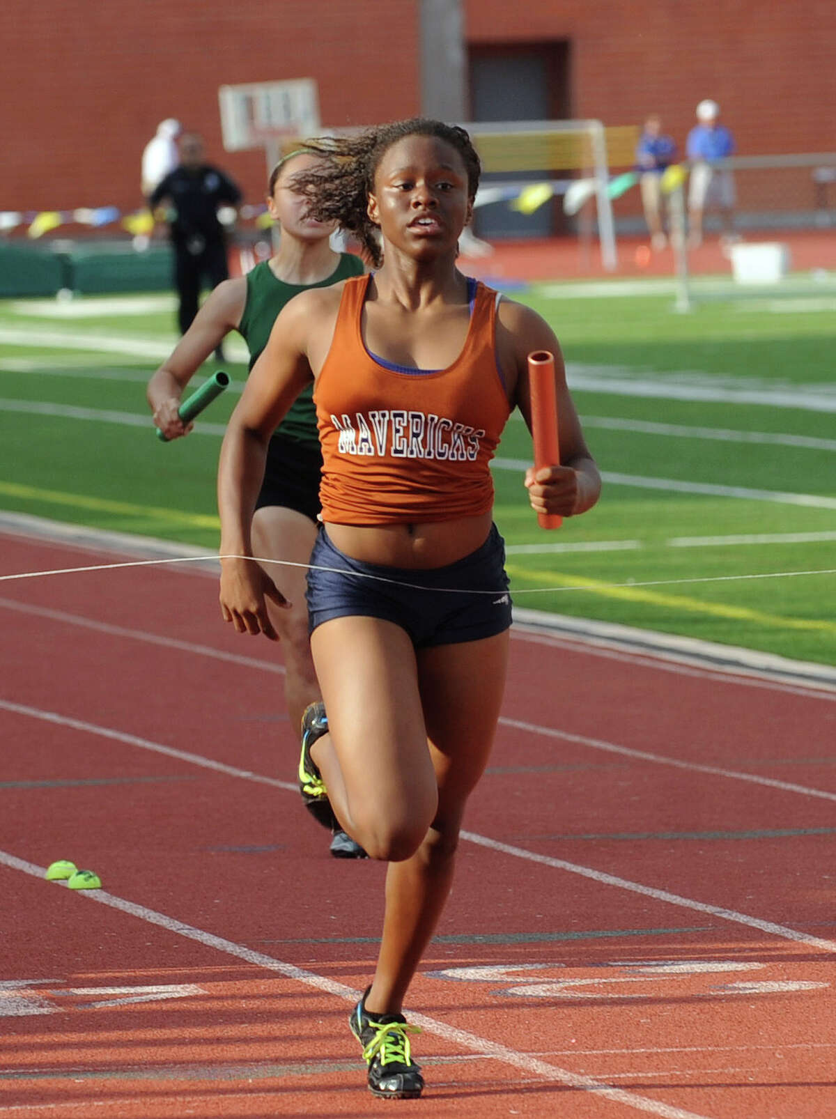 Yasmyn Richards of Madison crosses the finish line as her team wins the girls 4x100 meter relay during the finals of the District 26-5A track championships at Heroes Stadium on Thursday, April 12, 2012. Billy Calzada / San Antonio Express-News