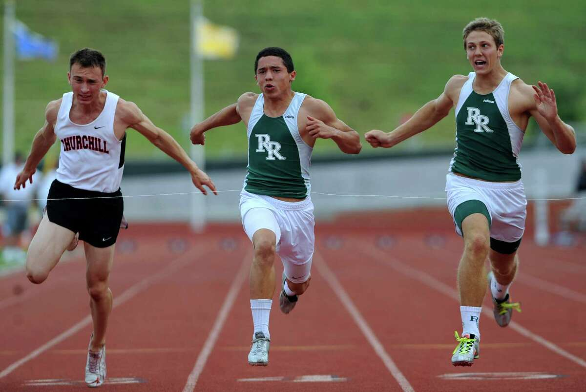 CJ Cavazos, middle, of Reagan High School, wins the 100-meter dash as Ryan Saavedra, left, of Churchill and Ty Branch of Reagan chase during the finals of the District 26-5A track championships at Heroes Stadium on Thursday, April 12, 2012. Billy Calzada / San Antonio Express-News