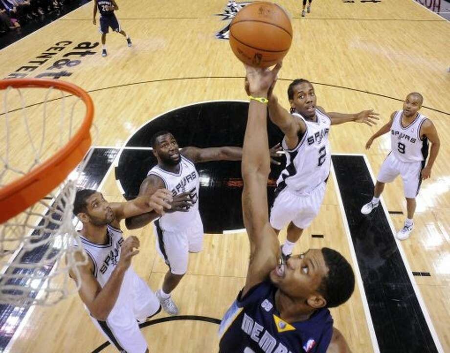 Memphis Grizzlies' Rudy Gay grabs for a rebound over the Spurs' Tim Duncan, DeJuan Blair, and Kawhi Leonard during second half action Thursday April 12,  2012 at the AT&T Center. The Spurs won 107-97.  (PHOTO BY EDWARD A. ORNELAS/SAN ANTONIO EXPRESS-NEWS) (EDWARD A. ORNELAS / SAN ANTONIO EXPRESS-NEWS)