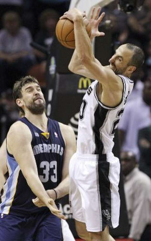 The Spurs' Manu Ginobili grabs a rebound over Memphis Grizzlies' Marc Gasol during second half action Thursday April 12,  2012 at the AT&T Center. The Spurs won 107-97.  (PHOTO BY EDWARD A. ORNELAS/SAN ANTONIO EXPRESS-NEWS) (EDWARD A. ORNELAS / SAN ANTONIO EXPRESS-NEWS)