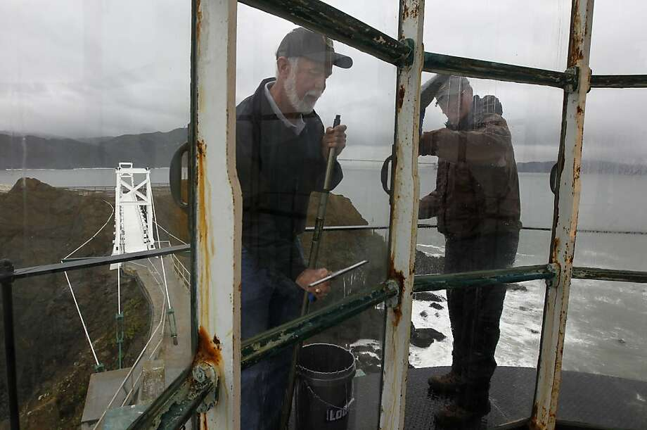 Mike Madden and Jim Brainerd clean windows of the Point Bonita lighthouse before it reopens this week, along with the rebuilt suspension footbridge (left). Photo: Paul Chinn, The Chronicle