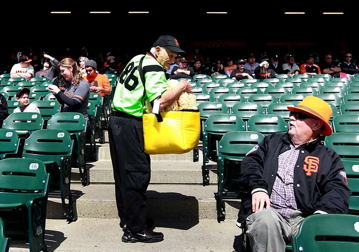 The Kettle Corn Man, who goes by the name Crazy Legs, talks with one of his Kettle Corn customers at AT&T Park prior to the start of the Giants baseball game with the Oakland Athletics, Wednesday, April 4, 2012. Crazy Legs is best known for his dances between innings while the music is playing.