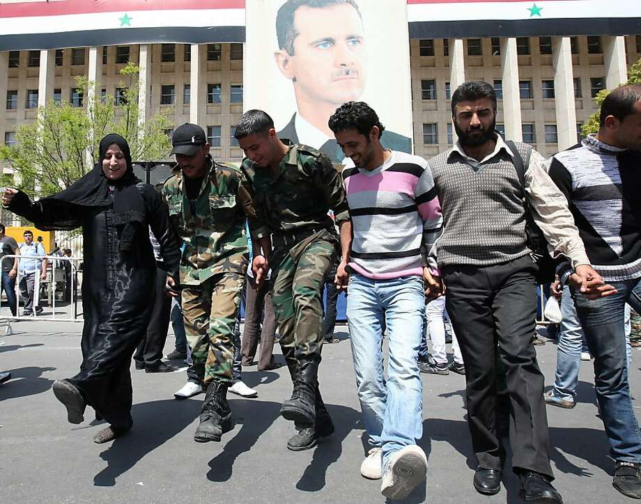 A Syrian woman dances with men in army fatigues in front of a portrait of Syrian President Bashar Al-Assad during a pro-regime rally in Damascus on April 12, 2012, as a UN-backed ceasefire went into effect. Forces loyal to Syrian President Bashar al-Assad shot dead a civilian in the central province of Hama, a monitoring group said, hours after a deadline to implement a ceasefire aimed to end 13 months of bloodshed. Photo: Louai Beshara, AFP/Getty Images