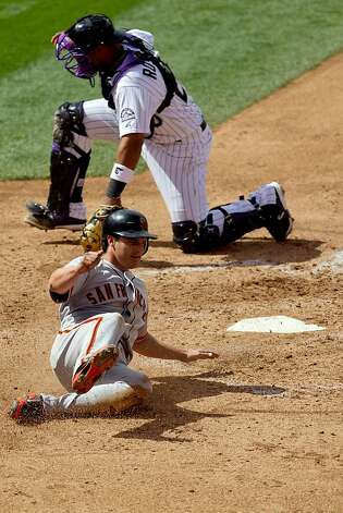 Ryan Theriot #5 of the San Francisco Giants slides past Wilin Rosario #20 of the Colorado Rockies to score at Coors Field on April 12, 2012 in Denver, Colorado. The Giants defeated the Rockies 4-2. Photo: Justin Edmonds, Getty Images
