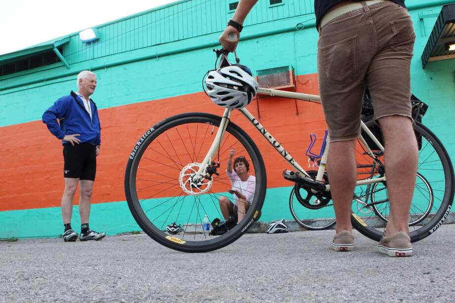 At Blue Line Bicycle Laboratory in the Heights, Jerry Kennedy, Jill  Nepomnick and Stephen Nowakowski prepare to ride to work. (Johnny  Hanson/Chronicle)