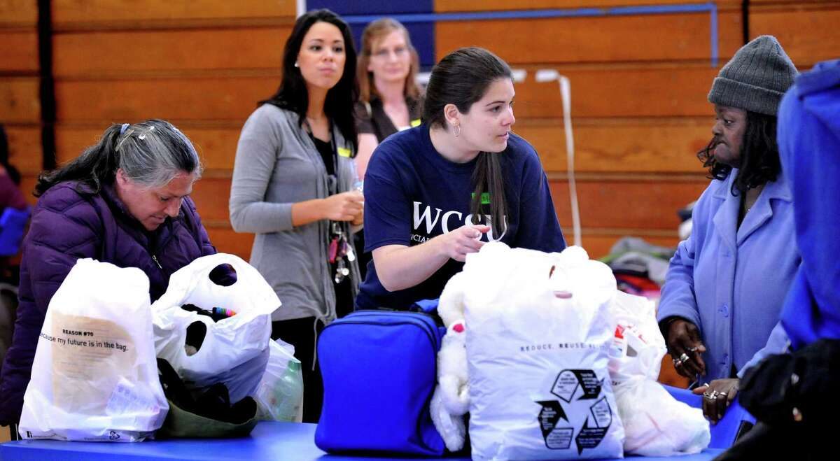 Volunteer Nicole McCormack, center, interacts with Leorna Garcia, right, as members of the Western Connecticut State University Social Work Senior Class Activities Committee host a