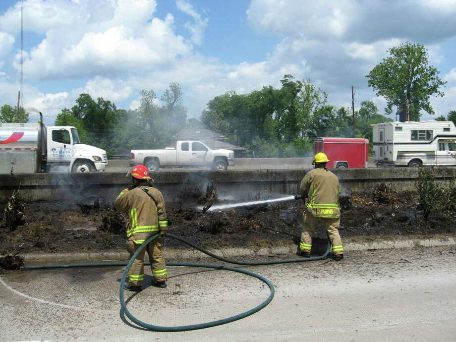 Beaumont firefighters Dustin Purvis and Capt. Mike Croaker extinguish a blaze alongside Interstate 10 at Ewing Street. It wasn't just brush. A discarded tire was in there, sending up black smoke as it burned. Dan Wallach/The Enterprise Photo: Dan Wallach
