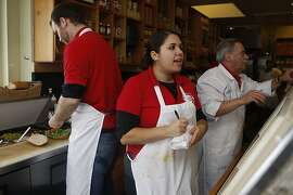 Mike McGee (left), Paula Guerra (middle), 20 years old, and John Franco Tuccori (right) working at Guerra Quality Meats in San Francisco, California, during the lunch hour on Friday, September 16, 2011.  Guerra's has been a family business for over fifty years.