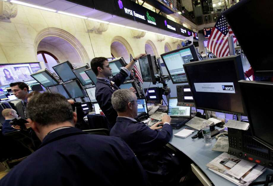 In a Feb. 24, 2012 photo traders work on the floor of the New York Stock Exchange Friday, Feb. 24, 2012.   U.S. stocks were also poised to fall on the open with Dow futures and S&P 500 futures both down 0.4 percent.  (AP Photo/Richard Drew) Photo: Richard Drew / AP