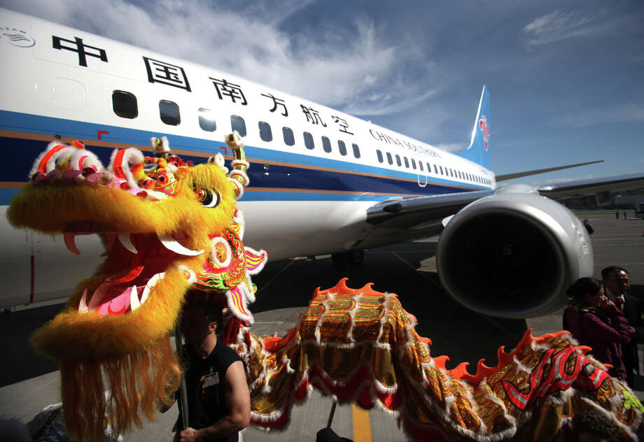 Dragon dancers with Mak Fai Washington Kung Fu Club stand next to Boeing's 4,000th Next-Generation 737 during the delivery ceremony for the 737 on Friday, April 13, 2012 at Boeing Field in Seattle. The plane, the best selling airliner in the world, was delivered to China Southern Airlines during the ceremony. Photo: JOSHUA TRUJILLO / SEATTLEPI.COM