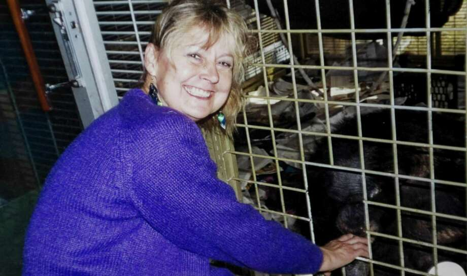 "Charla Nash in a 2007 photo next to the cage with the chimpanzee Travis. Travis mauled Nash in February 2009. While recognizing Charla Nash suffered ""profound"" injuries from an attack by a friend's pet chimpanzee, the Attorney General George Jepsen's office argues the state owes her nothing in part because of a loophole in law that allowed the animal to be kept in Stamford, according to a memorandem filed Friday April 13, 2012. Photo: Contributed Photo / Stamford Advocate Contributed"