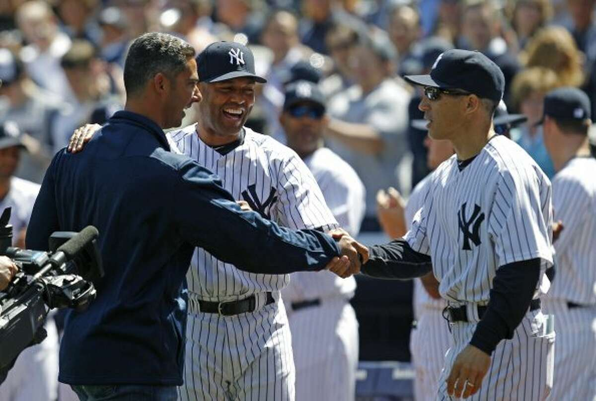New York Yankees manager Joe Girardi, right, greets retired New York Yankees catcher Jorge Podada, left, along with Yankees reliever Mariano Rivera after Posada threw out the ceremonial first pitch during the Yankees home opener baseball game against the Los Angeles Angels at Yankee Stadium in New York, Friday, April 13, 2012. (AP Photo/Kathy Willens) (AP)