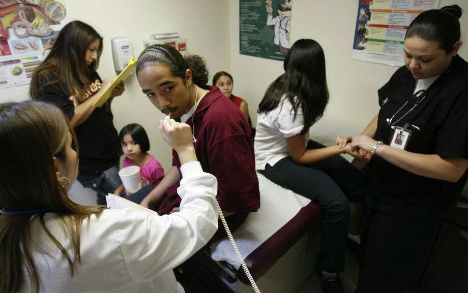 Una familia hispana del área de Houston, con niños que no tienen seguro médico, es atendida por personal médico durante una visita a la clínica Denver Harbor, en una foto de archivo. Photo: Sharon Steinmann / Houston Chronicle