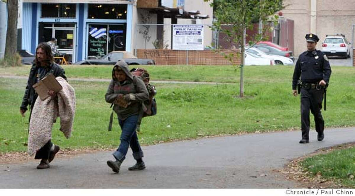 A police officer shooed away two transients from the Alvord Lake area near Stanyan and Haight Streets at Golden Gate Park in San Francisco, Calif. on Thursday, Sept. 20, 2007. PAUL CHINN/The Chronicle Ran on: 09-23-2007 A police officer shoos a pair of homeless people away from the Alvord Lake area near Stanyan and Haight streets late last week in Golden Gate Park. MANDATORY CREDIT FOR PHOTOGRAPHER AND S.F. CHRONICLE/NO SALES - MAGS OUT