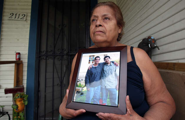 Santa Hernandez holds a picture of her son Mario Soto, Jr. (left) and her grandson Mario Soto III on the front porch of her West Side home Friday April 13, 2012. Hernandez's son was shot and killed by police last Wednesday afternoon at the Days Inn near Laredo street and Interstate-35. Police say the man was a suspect in six robberies. Photo: JOHN DAVENPORT, SAN ANTONIO EXPRESS-NEWS / SAN ANTONIO EXPRESS-NEWS (Photo can be sold to the public)