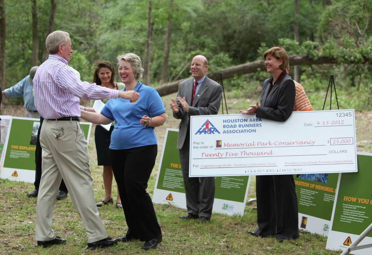 Joe Turner, director Houston Parks and Recreation Department, greets Mayor Annise Parker after a news conference at Memorial Park, where the Houston Area Road Runners Association donated $25,000 to start reforestation.