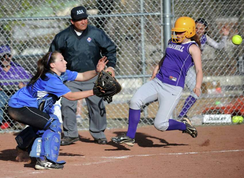 Darien's Olivia Gozdz reaches for the ball as Westhill's Tammy Wise slides into the plate during Friday's softball game at Westhill High School in Stamford on April 13, 2012.