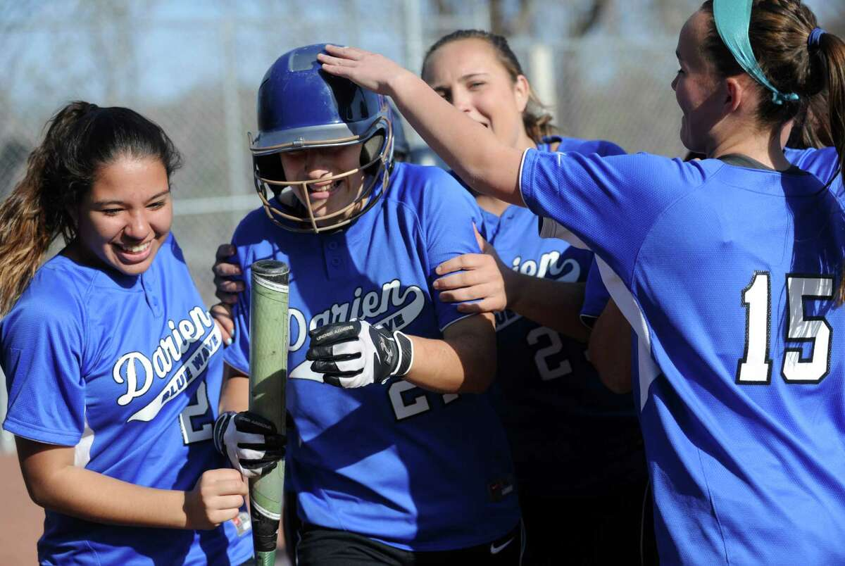 Darien teammates congratulate Erika Osherow after she hit a home run during Friday's softball game at Westhill High School in Stamford on April 13, 2012.