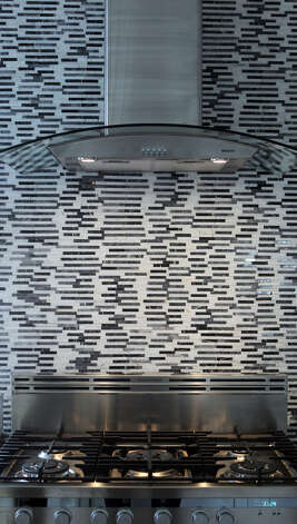 Stainless steel is the motif in the kitchen of the home of Freddie Delgado with an interesting backsplash behind the vent hood over the stove. (Wednesday April 11, 2012) John Davenport/San Antonio Express-News Photo: John Davenport