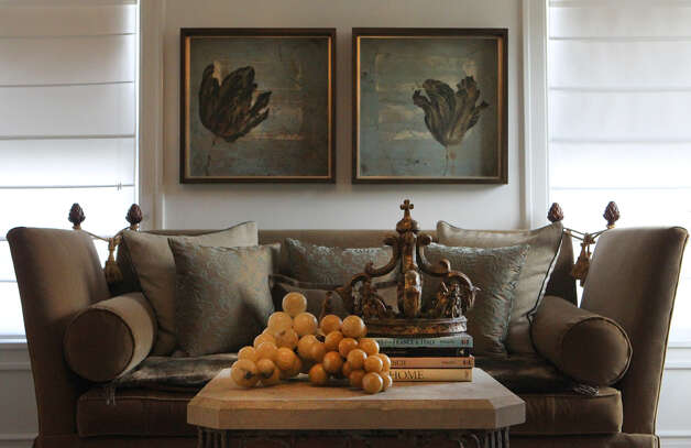 A sofa and table with attractive art work adorn the front living area in the Monticello home of Freddie Delgado. The home is going to be featured in the Fiesta Home Tour. (Wednesday April 11, 2012) John Davenport/San Antonio Express-News Photo: John Davenport