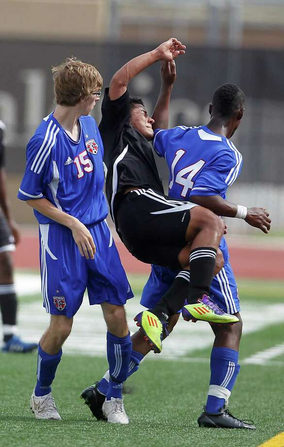 Sharpstown's Ever Sanchez (16) goes up for the header and gets tangled with Waco Midway's Evan Hebert (15) and Gerron Dewberry (14) during the first half of the Class 4A  Region III semifinal game between Sharpstown and Waco Midway at Turner Stadium Friday, April 13, 2012, in Humble. Photo: Karen Warren, Houston Chronicle / © 2012  Houston Chronicle