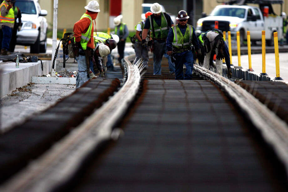 A construction team works on a section of Metro's North Line light rail extension on Fulton Street at Collingsworth Street earlier this year. The line will connect to the existing downtown Red Line. Photo: Johnny Hanson / © 2012  Houston Chronicle
