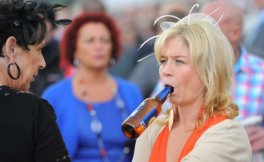 Hat not silly enough for Ladies Day at the Aintree Grand National Meeting in Aintree, England? No problem. Just drink a beer without using your hands. That will get you noticed. Photo: Andrew Yates, AFP/Getty Images