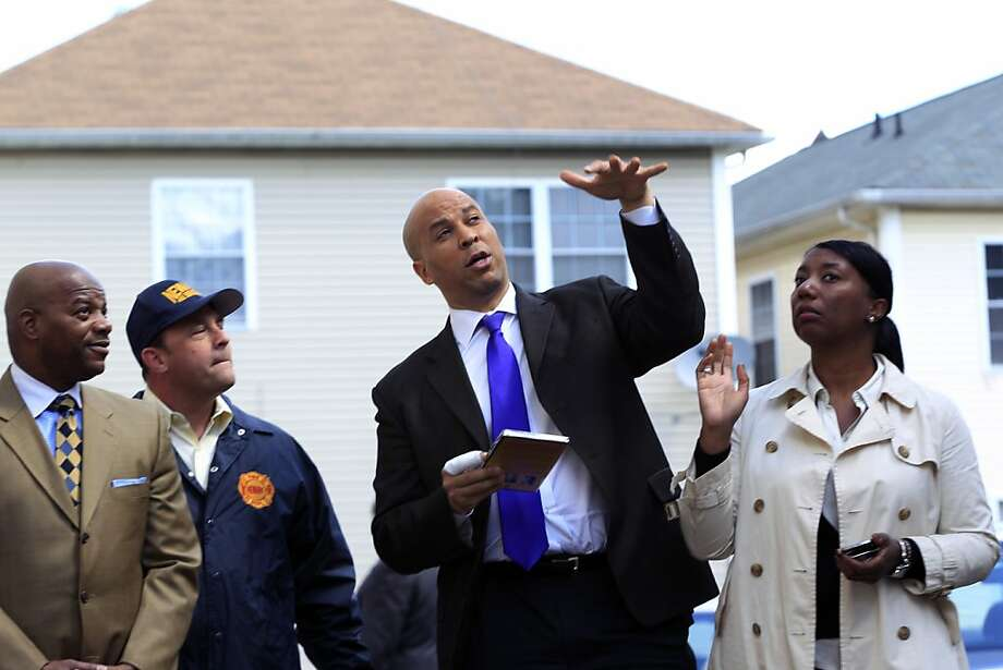 Newark Mayor Cory Booker, second right, has a bandaged right hand in front of a home in Newark, N.J., Friday, April 13, 2012, as he describes the scene Thursday when he rescued a woman from her burning home.  Booker said Friday he feared for his life as he helped rescue a neighbor from a fire before firefighters arrived. He described how he returned home Thursday night and saw his neighbor's home engulfed in flames. The woman Booker helped save is in stable condition. Photo: Mel Evans, Associated Press
