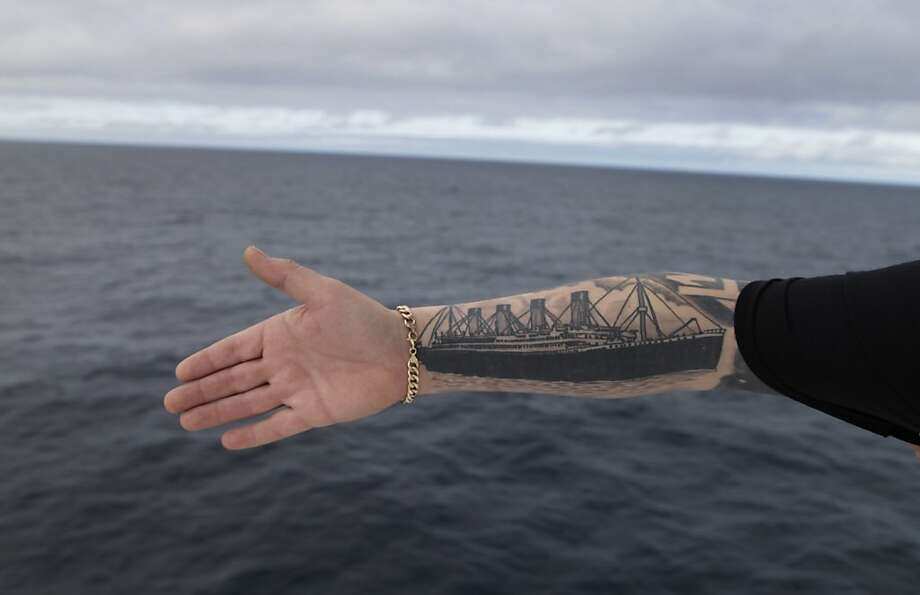 Derek Chambers from Belfast shows his tattoo of the Titanic, aboard the MS Balmoral Titanic memorial cruise ship in the Atlantic Ocean, Thursday, April 12, 2012. Nearly 100 years after the Titanic went down, the cruise with the same number of passengers aboard is setting sail to retrace the ship's voyage, including a visit to the location where it sank. The Titanic Memorial Cruise departed Sunday, April 8, from Southampton, England, where the Titanic left on its maiden voyage and the 12-night cruise will commemorate the 100th anniversary of the sinking of the White Star liner. With 1,309 passengers aboard, the MS Balmoral will follow the same route as the Titanic and organizers are trying to recreate the onboard experience minus the disaster from the food to a band playing music from that era. Photo: Lefteris Pitarakis, Associated Press