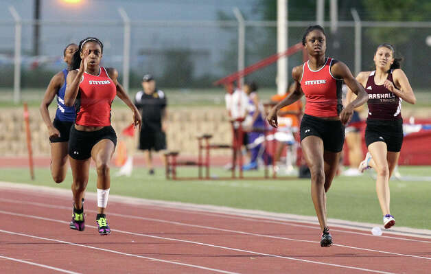 Stevens' Kiana Horton (left) edges out teammate Elexus Allen for first place in the 200-meter dash at the District 27-5A track meet at Gustafson Stadium on Friday, Apr. 13, 2012. Kin Man Hui/Express-News. Photo: Kin Man Hui, Kin Man Hui/Express-News / ©2012 San Antonio Express-News