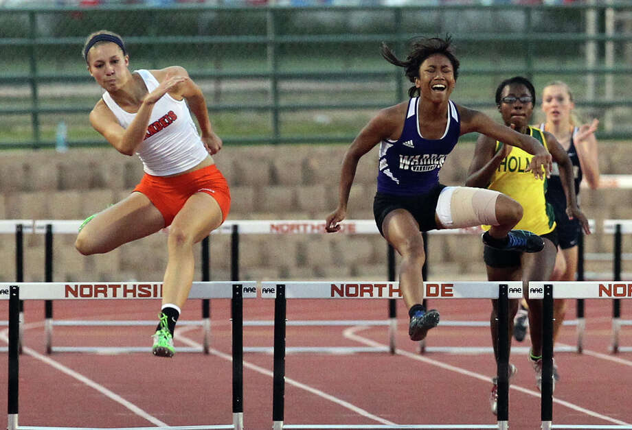 Brandeis' Kyndall Snider (left) takes first place from Warren's Jerica Love in the 300-meter hurdles at the District 27-5A track meet at Gustafson Stadium on Friday, Apr. 13, 2012. Kin Man Hui/Express-News. Photo: Kin Man Hui, Kin Man Hui/Express-News / ©2012 San Antonio Express-News