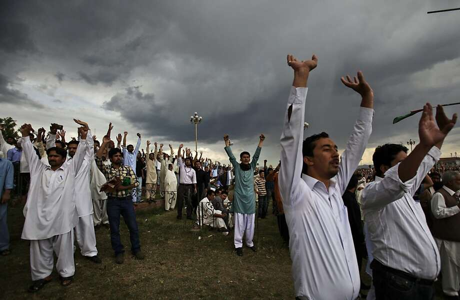 Pakistani Shiite Muslims raise their hands and chant slogans during a protest to condemn the recent killings of Shiites in northern Pakistan and Quetta, near the parliament, in Islamabad, Pakistan, Friday, April 13, 2012. Hundreds of Shiite Muslims gathered in the capital demanding protection for their community who are frequently targeted by alleged militants. (AP Photo/Muhammed Muheisen) Photo: Muhammed Muheisen, Associated Press