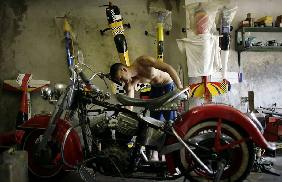 "Yaismer Escalona works on a Harley Davidson in Havana, Cuba, Friday April 13, 2012.  Cuban Harley Davidson owners and enthusiasts will gather this weekend for the island's first-ever national gathering in honor of the ""hog"" in the tourist resort city of Varadero. (AP Photo/Javier Galeano) Photo: Javier Galeano, Associated Press"
