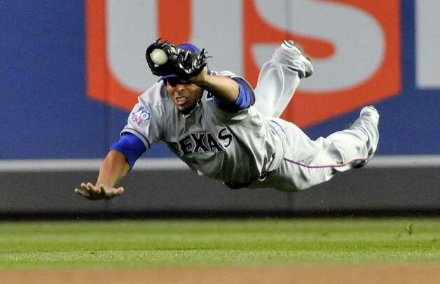 Texas Rangers right fielder Nelson Cruz makes a diving catch on a shallow fly ball off the bat of Minnesota Twins' Jamey Carroll in the first inning of a baseball game Friday, April 13, 2012, in Minneapolis. Photo: AP