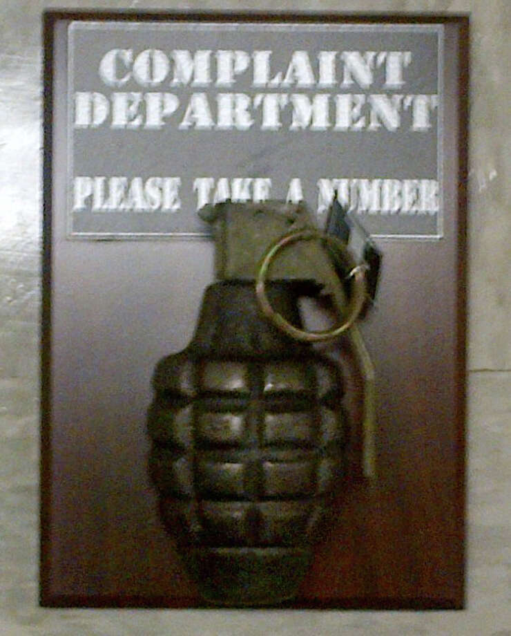 "This Thursday, April 12, 2012 photo provided by the New York City Police Department shows a novelty grenade mounted on a plaque that reads ""Complaint department: Take a number."" An office building near ground zero in New York was evacuated after the replica grenade was discovered in a package of the building's mailroom. (AP Photo/New York Police Department)"