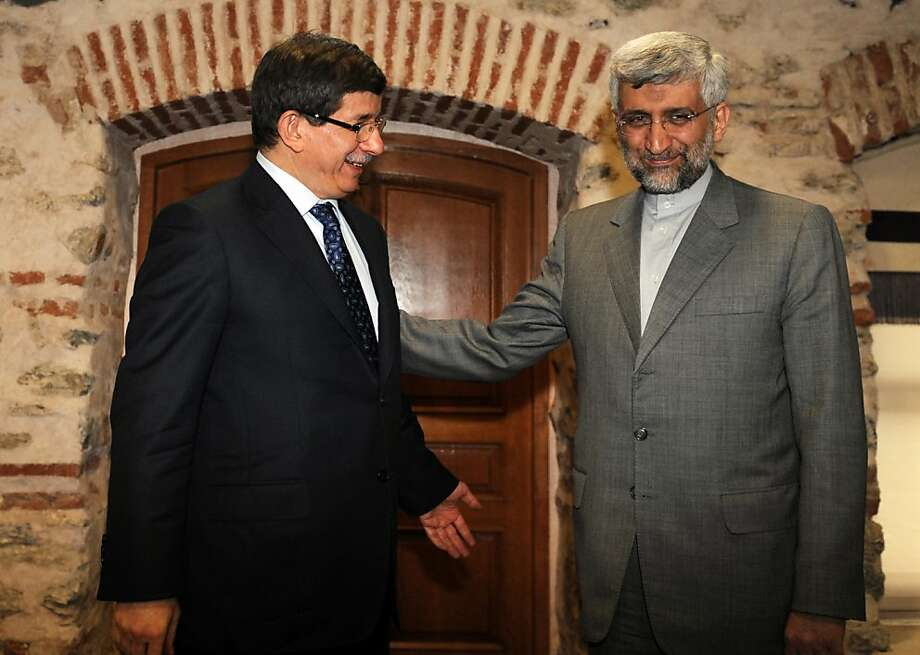 """Turkish Foreign Minister Ahmet Davutoglu (L) poses with Iran's top national security official, Saeed Jalili before their meeting on April 13, 2012 in Istanbul on the eve of the resumption of talks between the European Union and Iran about its nuclear program. A new round of nuclear talks between Iran and representatives of the """"Iran Six"""" nations will resume on April 14 in Istanbul after a 13-month hiatus. The other members of the """"Iran Six"""" - also known as the P5+1 - are Russia, China, the United States, France, the United Kingdom and Germany. Photo: Bulent Kilic, AFP/Getty Images"""